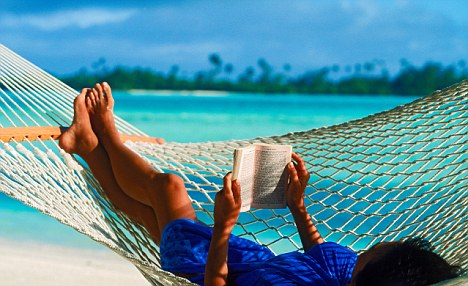 Woman in hammock on island holiday reading paperback book